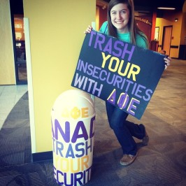 Delta Phi Epsilon sister Brenna Rathsack posing next to the Trash Your Insecurities stand.